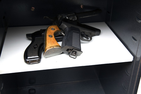 three pistols in the open safe