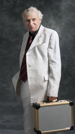 businessman in a white suit with case on gray  photo
