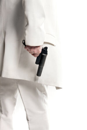 grabbing at the back: businessman in a white suit holding a gun Stock Photo