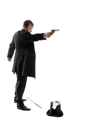 gentlemen in a jacket holding gun in his hand ,hat lying on the floor