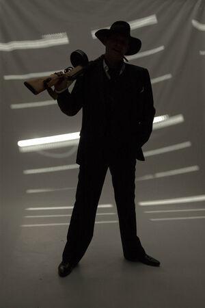 businessman in hat with a gun in dark room