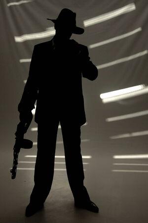 gun room: businessman in hat with a gun in dark room
