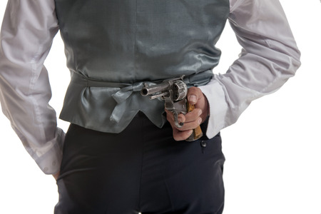 gentlemen in a jacket holding gun in his hand.View from the back