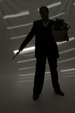 gun room: businessman in suit and hat with gun hold basket with personal belongings in dark room