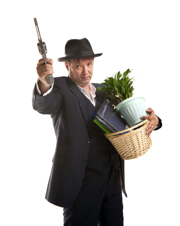 belongings: businessman in suit and hat with gun hold basket with personal belongings on white background Stock Photo