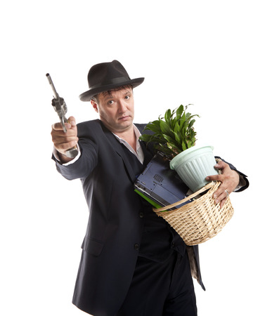 businessman in suit and hat with gun hold basket with personal belongings on white background Stock Photo