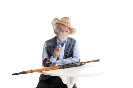 elderly man in a hat sitting at a table with a gun and smokes a cigarette on a white background photo