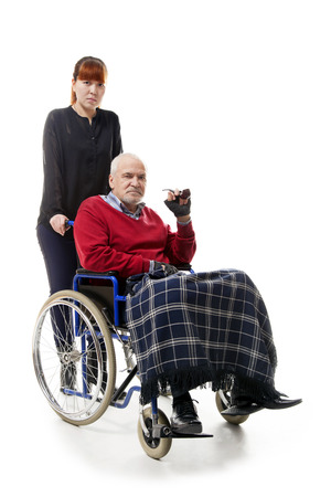 eldercare: old man on wheelchair with younger woman Stock Photo