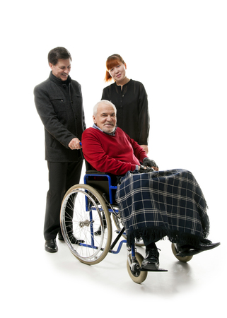 eldercare: old man on wheelchair with younger man and woman