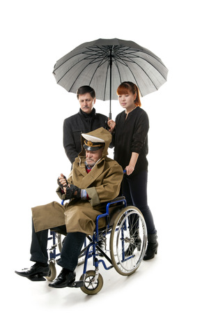 mobility nursing: old man on wheelchair with younger man and asian woman Stock Photo