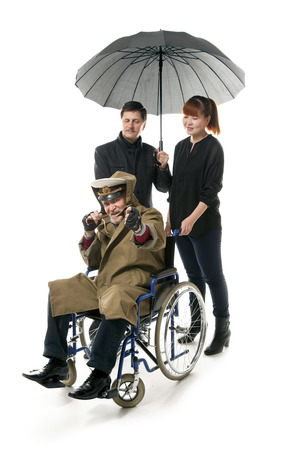 younger man: old man on wheelchair with younger man and asian woman Stock Photo
