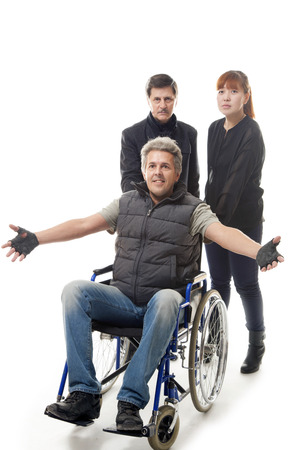 man on wheelchair with younger man and woman Stock Photo