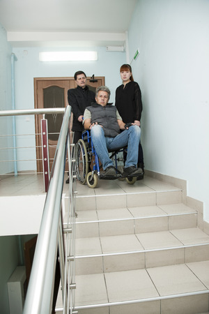 younger man: man on wheelchair with younger man and woman Stock Photo