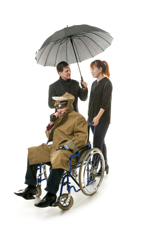 eldercare: old man on wheelchair with younger man and asian woman Stock Photo
