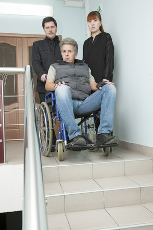 mobility nursing: man on wheelchair with younger man and woman Stock Photo