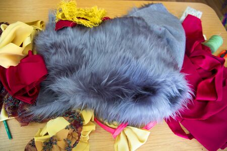 remnants: close-up of gray fur, colorful fabrics on wooden table Stock Photo