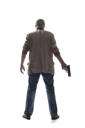 銃で黒手袋の男。白い背景で隔離の手で銃を持つ黒手袋の男の背面図