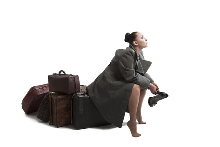 greatcoat: Beautiful young woman with retro style suitcases in military greatcoat