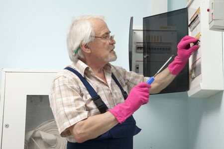 contador electrico: Elder man fixing an electric meter in pink gloves