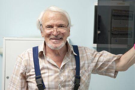 contador electrico: viejo hombre que se está preparando para fijar un medidor eléctrico Foto de archivo
