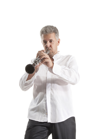 clarinete: mature man in hat playing clarinet on white studio backround Foto de archivo