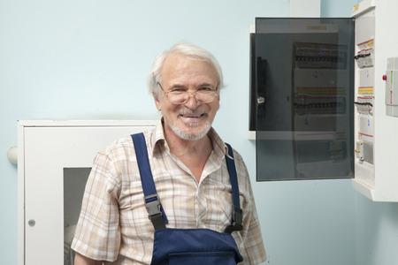 electric meter: viejo hombre que se está preparando para fijar un medidor eléctrico Foto de archivo