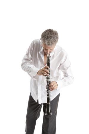 clarinet: mature man in hat playing clarinet on white studio backround Foto de archivo
