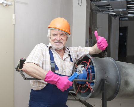 hand tool: Elder man fixing an industrial heater in orange helmet and pink gloves with wrench Stock Photo