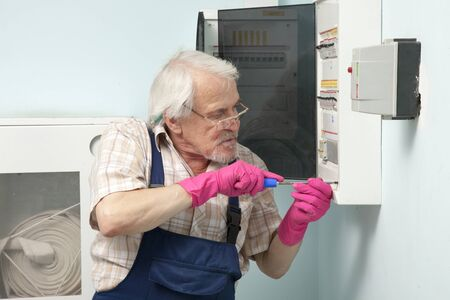 electric meter: Elder man fixing an electric meter in pink gloves
