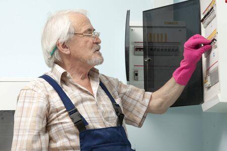 mounting: Elder man fixing an electric meter in pink gloves