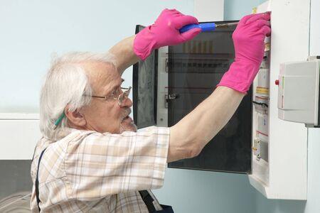 electric meter: Un más viejo hombre que se fija un medidor de electricidad en los guantes de color rosa Foto de archivo