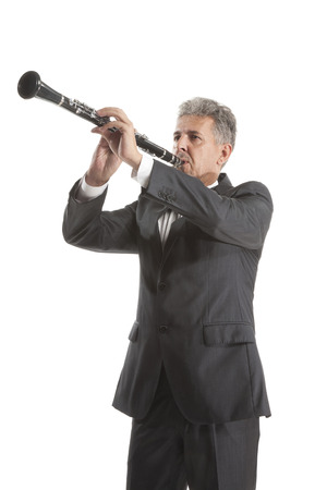 clarinet: Mature man playing clarinet on white studio backround