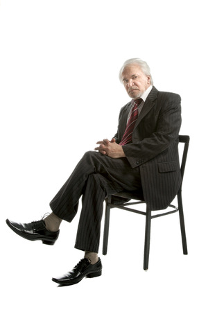 middle aged men: Senior businessman sitting on a chair  isolated over white background