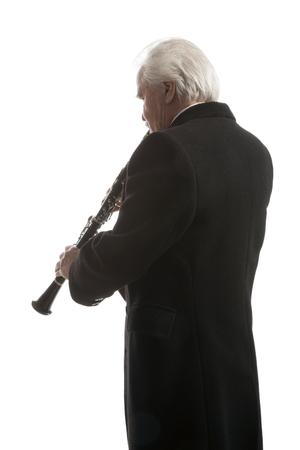clarinete: mature man in coat playing clarinet on white studio backround Foto de archivo