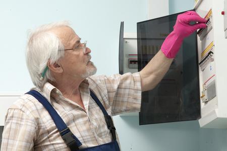 contador electrico: Un más viejo hombre que se fija un medidor de electricidad en los guantes de color rosa Foto de archivo