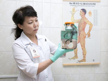 sanguijuela: Doctor que sostiene un recipiente de vidrio con sanguijuelas en el fondo del cartel con una imagen de los puntos de acupuntura humanos. Foto de archivo