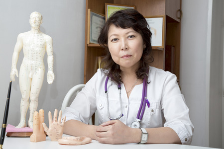 complementary therapies: Doctor girudoterapevt on background dummy with acupuncture points.