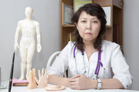 hemorragia: girudoterapevt médico en el fondo maniquí con los puntos de acupuntura.