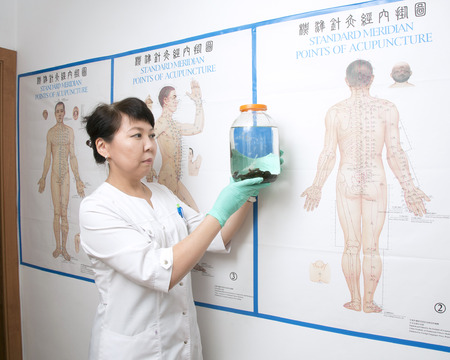 Doctor holding a glass vessel with leeches on the background of the poster with a picture of human acupuncture points. Stock Photo