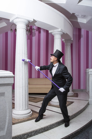 servant: Servant in a frock coat and top hat engaged in cleaning expo hall