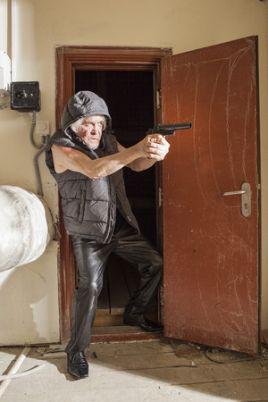 Armed with a gun bandit pursues a sacrifice in the attic Stock Photo