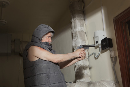 outcast: Armed with a gun bandit pursues a sacrifice in the attic Stock Photo