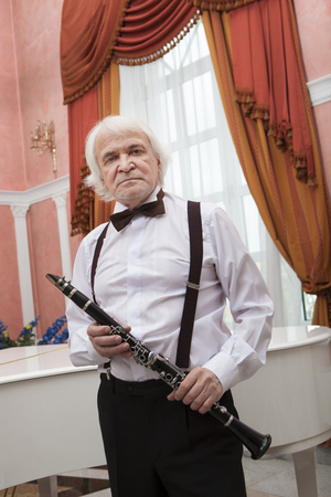 Vigorous charming aging musician plays the clarinet