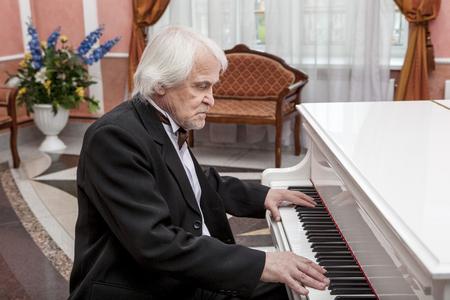 vigorous: Vigorous charming aging musician playing the white piano