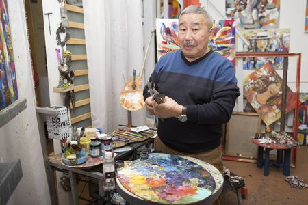 expressionist: Expressionist artist in the interior of his art studio among his paintings