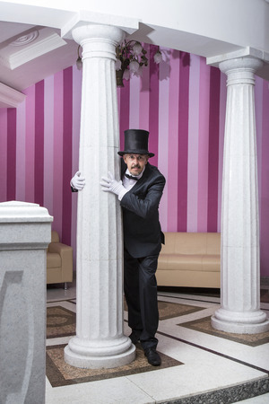 the exhibition hall: Servant in a frock coat and top hat posing for a photograph in the exhibition hall