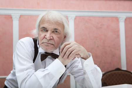 conservatory: Vigorous charming aging musician playing the white piano
