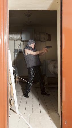 guerrilla: Armed with a gun bandit pursues a sacrifice in the attic Stock Photo
