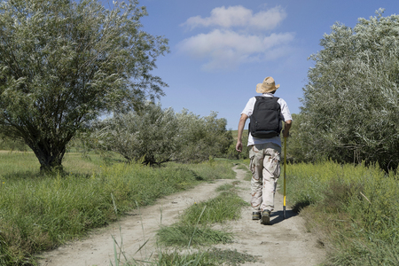 Young adult man tourist with a backpack walking on rural road