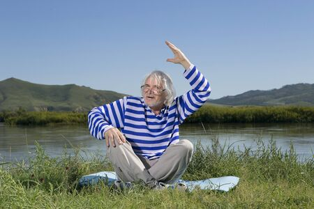 Senior man in a striped blouse resting and meditating on the river bank